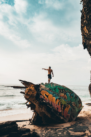 man,  pointing,  ocean,  beach,  sand,  rock,  grafitti,  paint,  art,  design,  blue sky,  sea,  wave,  travel,  summer,  vacation,  holiday