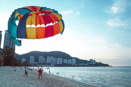 nature, beach, shore, sand, water, ocean, waves, splash, paragliding, parachute, people, buildings, resort, mountain, slope, sky, clouds, horizon