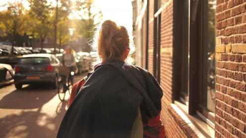 people, woman, bun, sunny, walk, street, building, apartment, green, trees, stroll