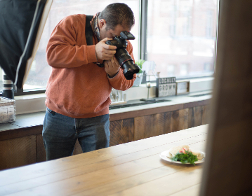 photographer,  picture,  photo,  photograph,  man,  male,  camera,  lens,  food,  food photography,  working,  table,  window,  professional, person, restaurant