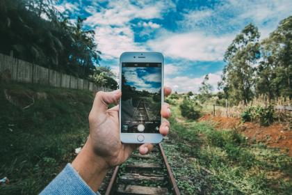 technology, gadgets, iphone, smartphone, mobile, nature, forests, trees, grass, train, rails, tracks, sky, clouds, horizon, guy, man, hands, hold, photography