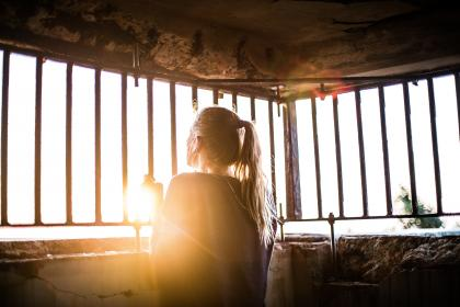 woman, girl, lady, people, back, contemplate, stand, grasp, steel, bars, concrete, room, confined, sun, light, leaks, flare