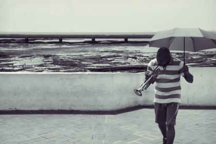 Panama, guy, man, people, trumpet, musician, music, umbrella, shorts, ocean, sea, water, black and white