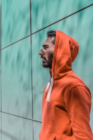 man, casual, portrait, hoodie, sweatshirt, beard, person, alone, building, exterior, outdoors, staring, red, sunlight