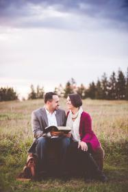 people, couple, man, woman, smile, happy, sitting, green, grass, book, bible, reading, outdoor, trees, plants, sky, clouds