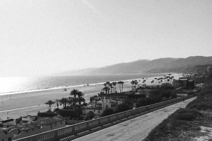 beach, boardwalk, sand, ocean, sea, shore, palm trees, houses, mountains, coast, black and white