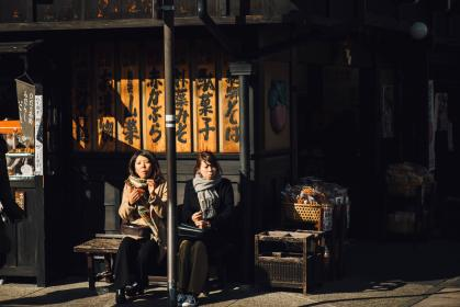 people, woman, lady, sister, post, bench, steel, wooden, building, old, establishment, store, food, sunshine, day, shadow, sidewalk