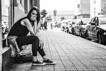 black and white, woman, girl, alone, sitting, waiting, street, car, vehicle, parking, city, building, structure