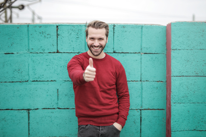 man,  thumbs up,  happy,  smile,  red,  jumper,  jersey,  blue,  brick,  wall.jeans,  fashio,  male,  people