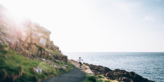 people, guy, travel, skateboarding, sport, road, path, coast, sea, ocean, water, rocks, hill, horizon, cliff, green, gass