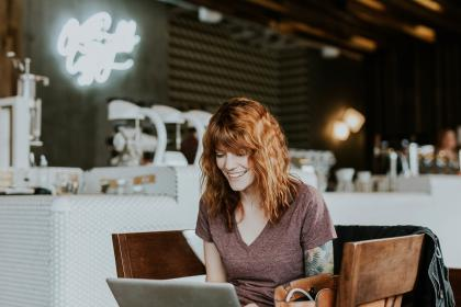 laptop, electronic, gadget, communication, research, internet, browser, business, woman, people, smile, happy, restaurant, table, chair, inside, blur, signage