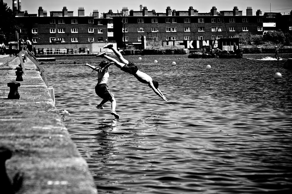 diving swan dive swimming water people boy girl buildings city black and white