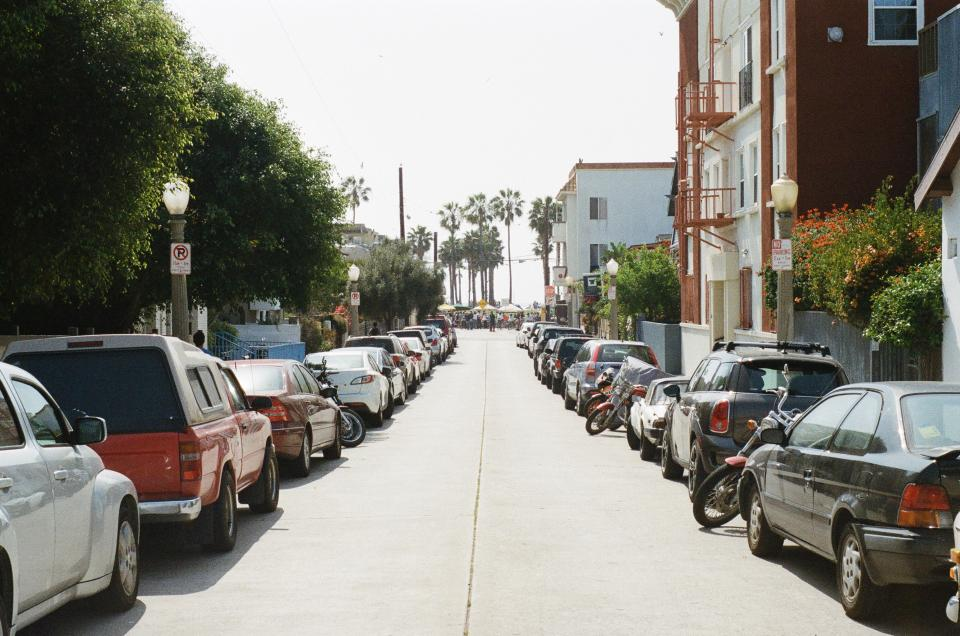 street parking cars trucks motorcycle houses apartments buildings palm trees sunshine