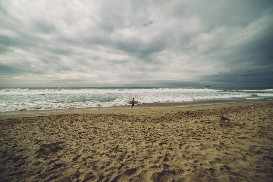 beach sand ocean sea waves surfer surfboard cloudy clouds