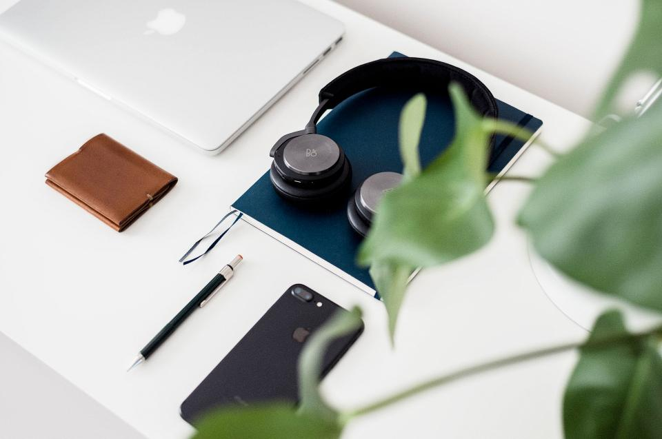 white table apple mobile phone wallet headphone laptop macbook book business office green plant pen