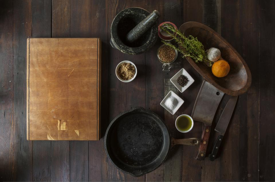 wood cuttingboard grinder spices pot castiron salt pepper oil vegetables fruit food ingredients butcher knife knives garlic orange
