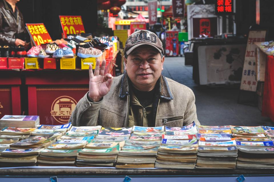 Chinese old man elderly books store shop market merchandise shoes Tianjin China