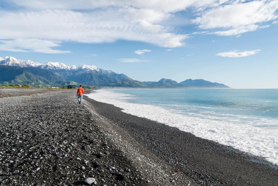 people man walking alone sea ocean water waves beach shore coast sand blue sky clouds mountain landscape view nature