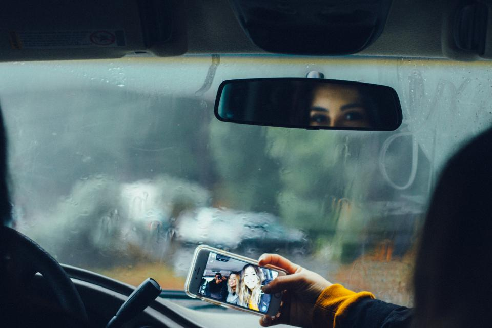 car drive glass raindrops wet raining travel trip people friends family outing bonding vacation mobile phone camera selfie photography