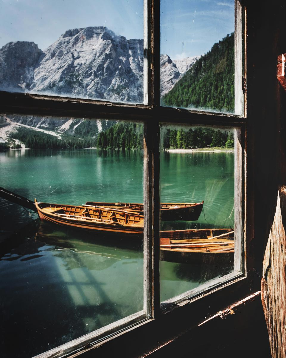 lake water wooden boat outdoor window glass frame sunny day mountain trees plant valley hill landscape view