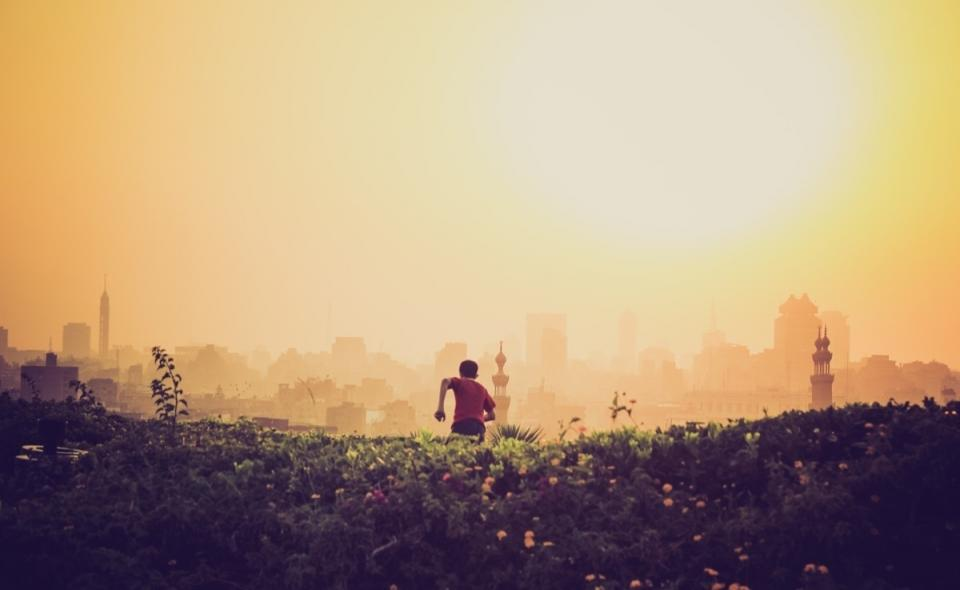 yellow sky sun boy running grass fields buildings city