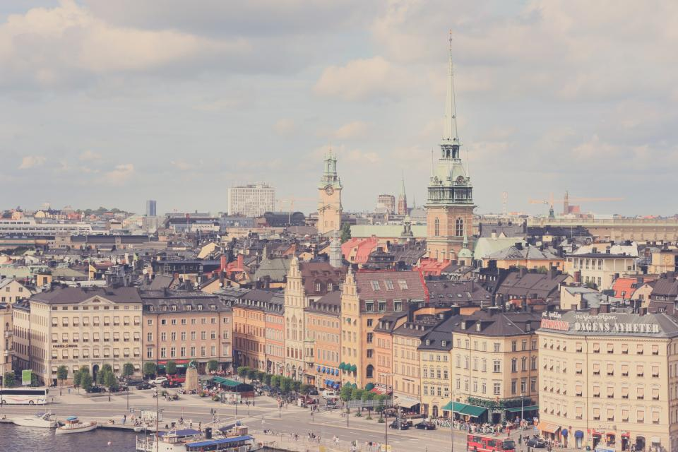 city buildings roads street water boats skyline view stockholm sweden shops stores people signs busses square towers