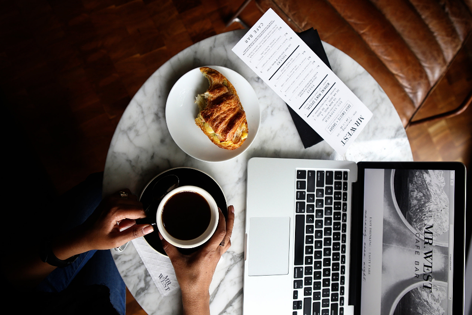 breakfast pastry coffee laptop table marble hands people person food drink black cup plate