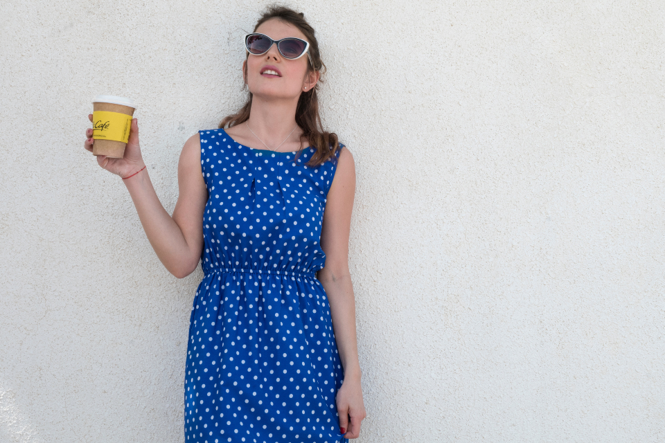 woman blue dress hold drink coffee food fashion style sunglasses polka dots pose model
