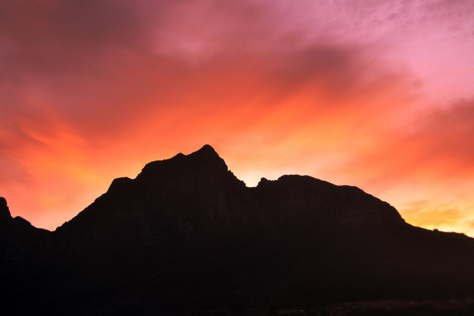 nature landscape mountains summit peaks sky horizon clouds fiery gradient shadows silhouette orange purple
