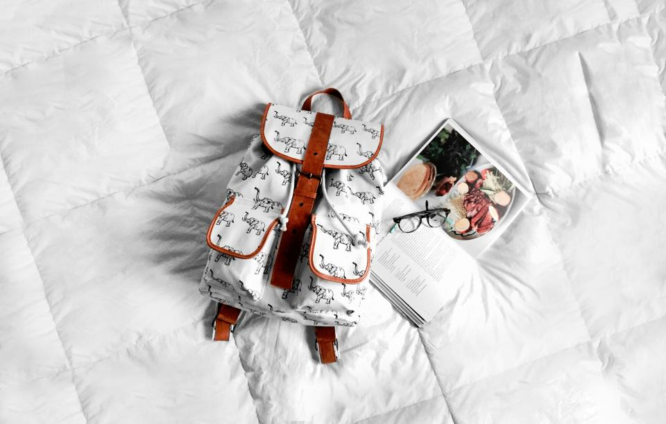 white bed bag backpack book glasses lifestyle travel