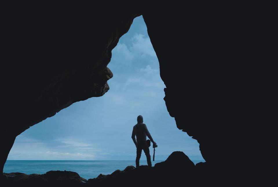 people man travel adventure camera alone shadow cave blue water ocean sea