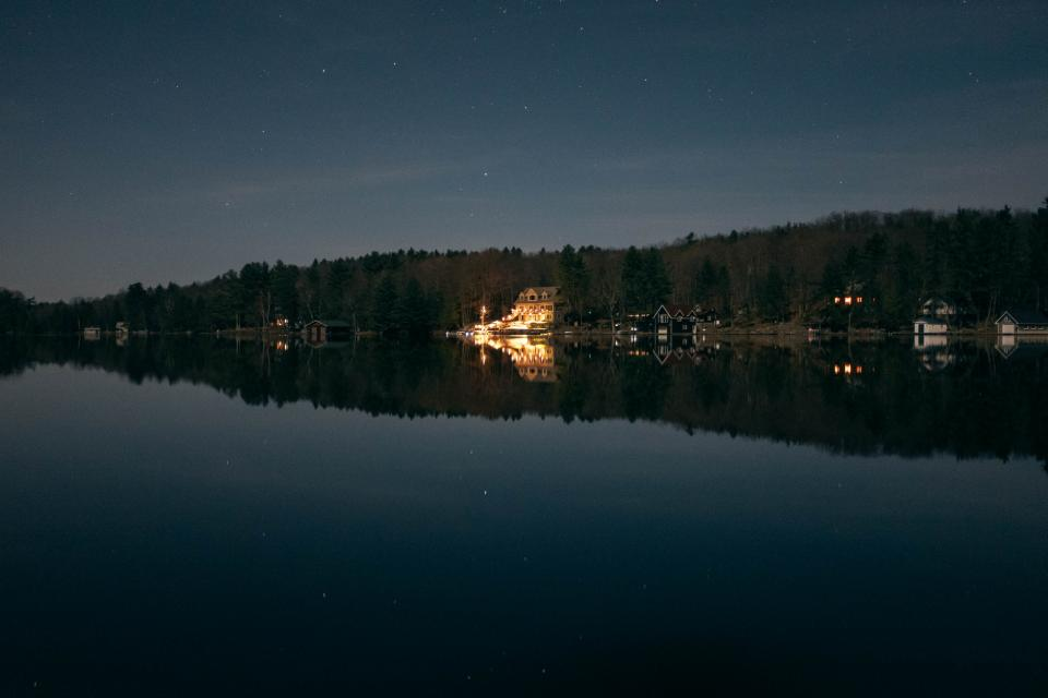lake water reflection houses night sky trees outdoors stars