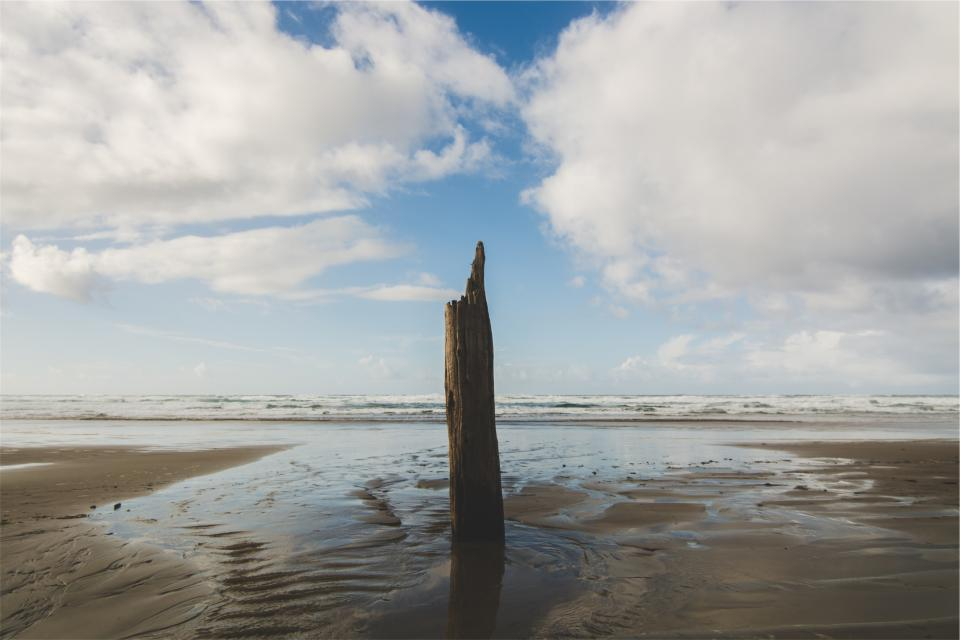 wood post beach sand shore water ocean sea sky clouds