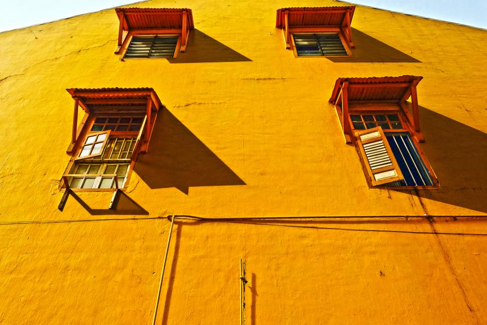 yellow wall building windows shutters architecture