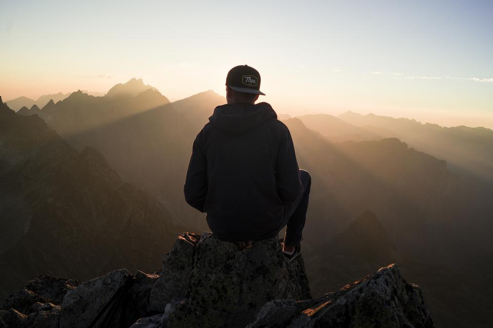guy man male people back contemplate sit nature mountains rocks travel trek hike climb summit peaks fog sky horizon gradient