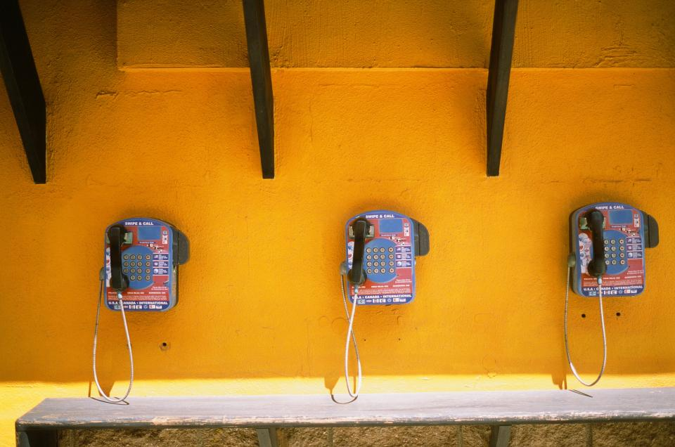 telephones payphones yellow wall collect call