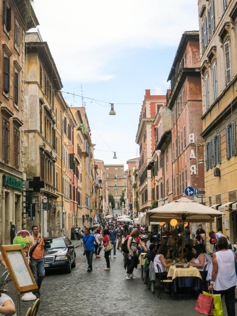 Rome Italy city streets cobblestone people pedestrians restaurants eating buildings houses apartments architecture crowd