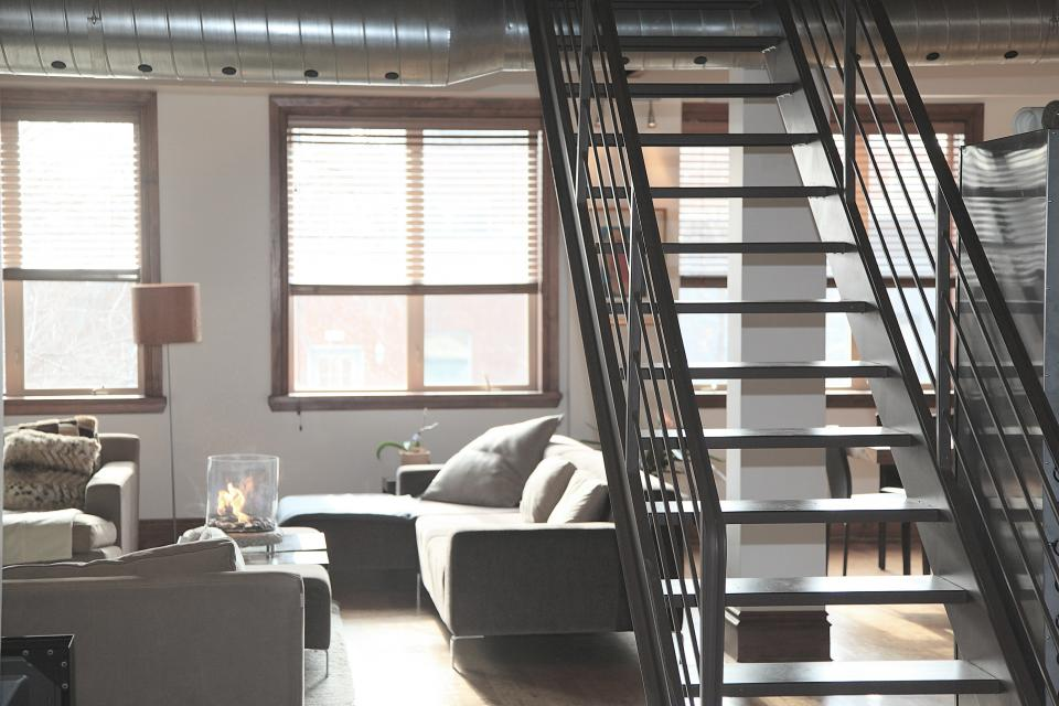 condo loft apartment house stairs steps hardood floors couches lamps windows blinds vents pipes railing furniture