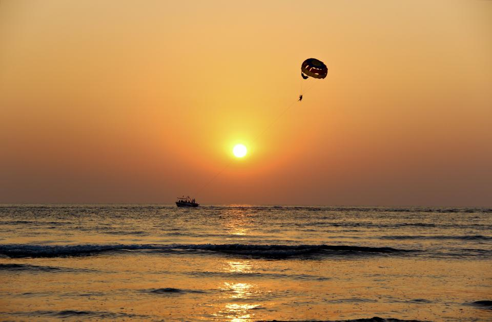 nature water ocean sea reflection boat paragliding parachute sunset sunrise sky horizon clouds gradient yellow gray
