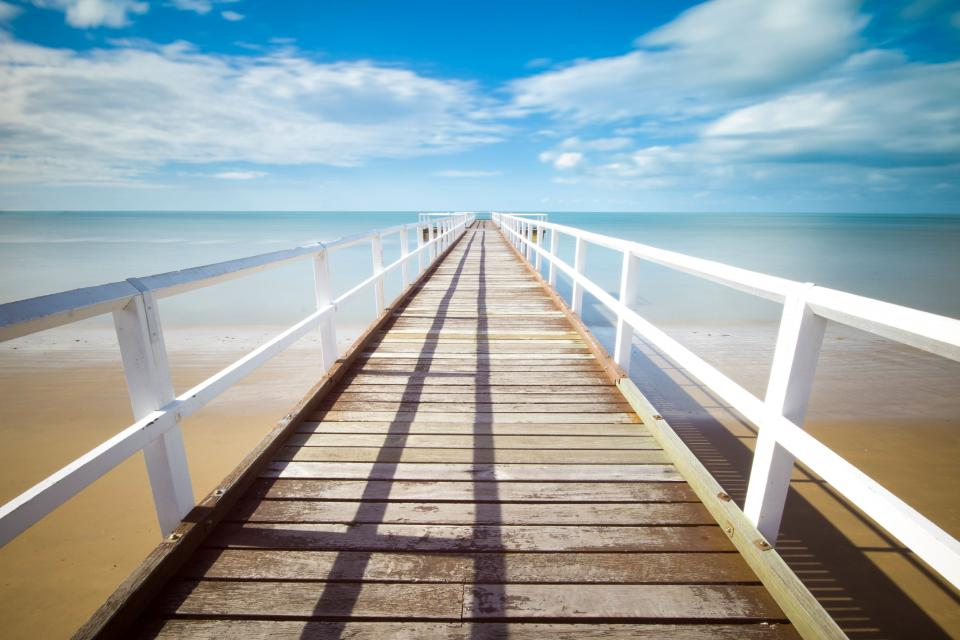 beach sand tropical dock pier railing wood ocean sea water sky clouds