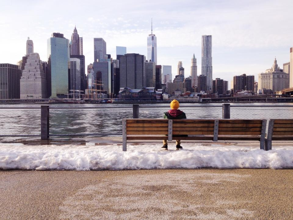 new york city buildings towers skyscrapers skyline view boy man bench water waves cold winter