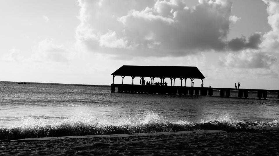 black and white sky clouds beach sand water waves pier
