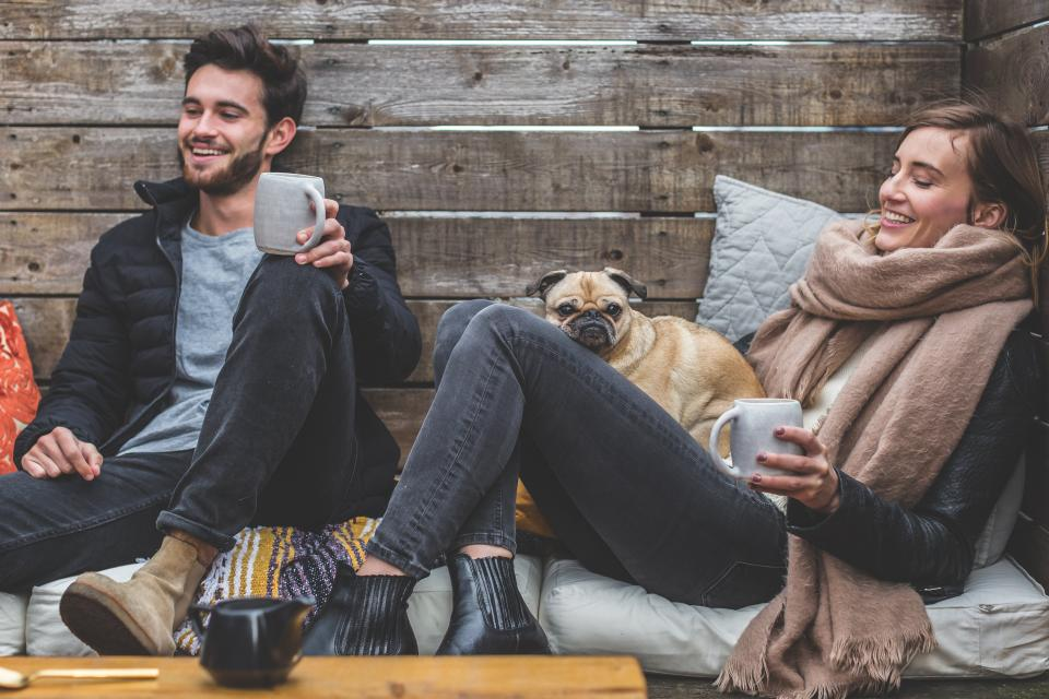 people man woman happy couple coffee break relax smile sitting pug dog puppy pet outdoors