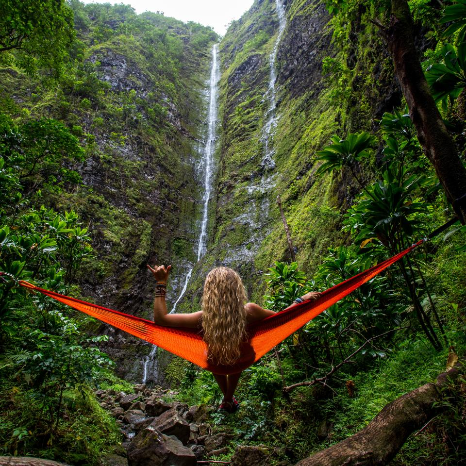 nature landscape mountains lush vegetation plants branches trees waterfalls rocks stream woman lady people hammock travel trek climb