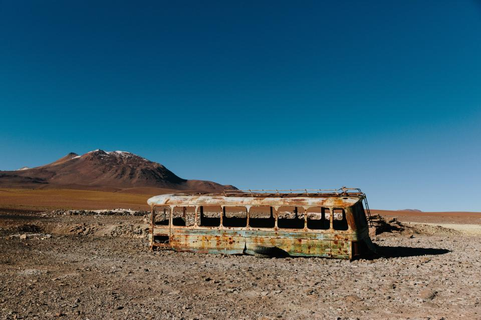 desert sand rocks blue sky bus abandoned damaged rust nature landscape mountain