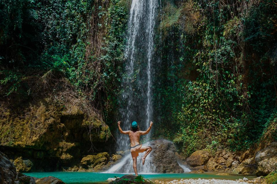 waterfalls green grass trees plants rocks nature outdoor people man guy swimming