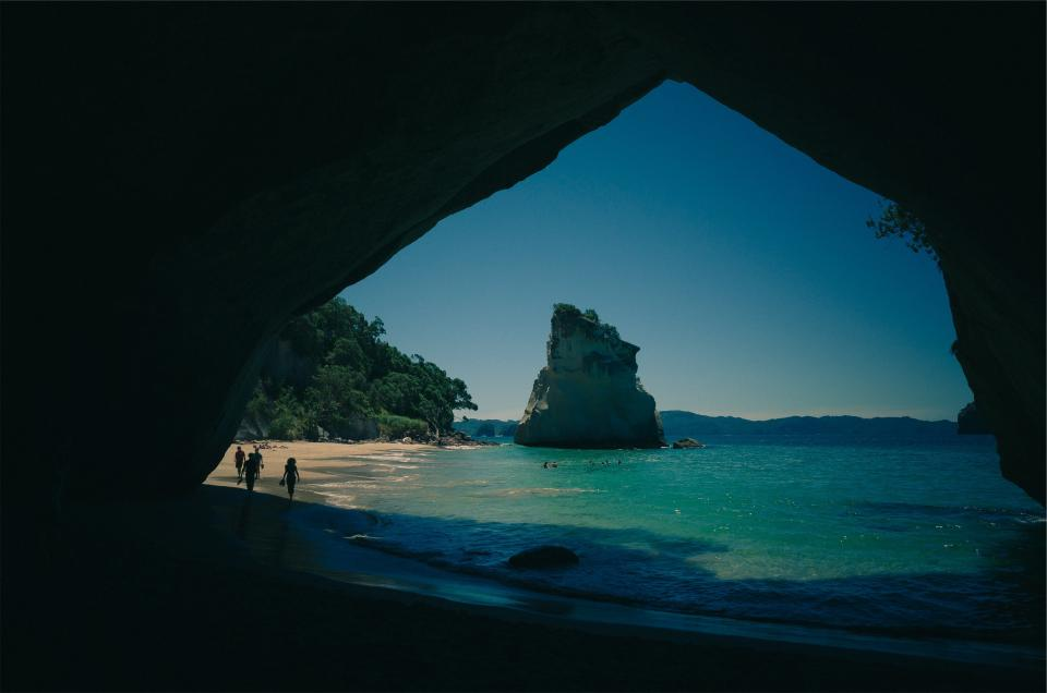 cave beach sand water coast shore ocean sea tropical rocks people