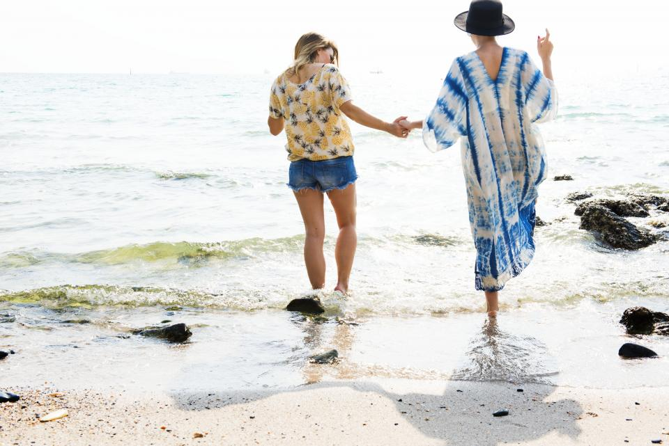 people girls female ladies women friends holding hands travel outdoor alone beach seashore sea ocean waves water summer vacation