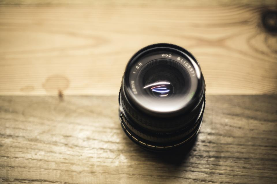camera lens black photography wooden table blur