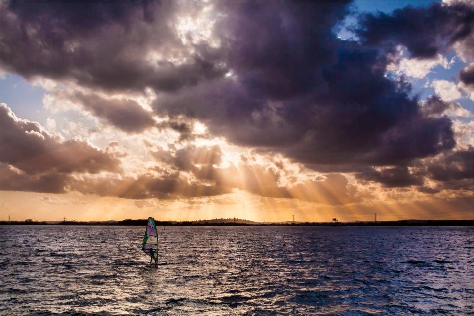 sunbeams sky clouds sunset windsurfing water ocean sea